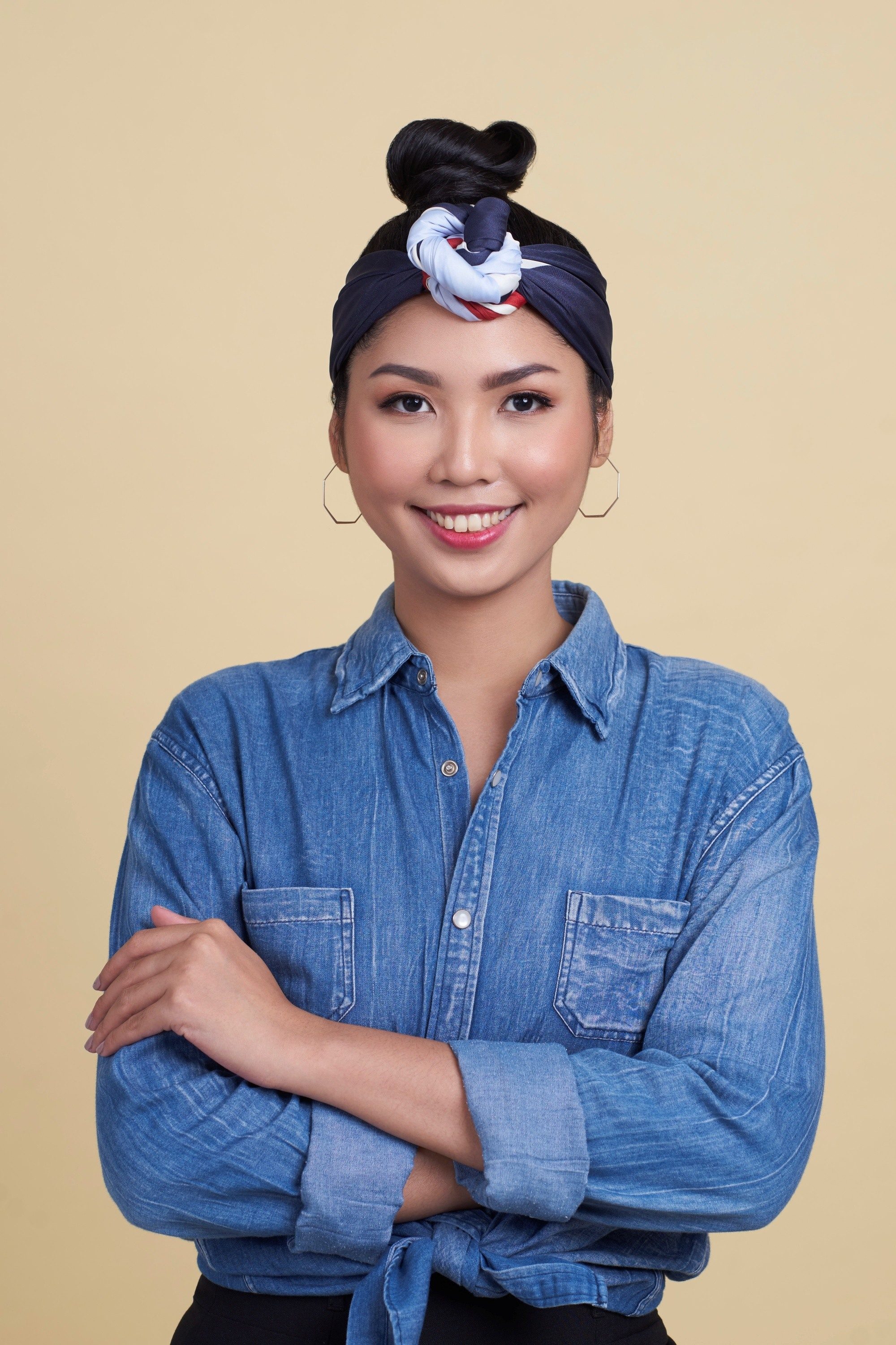 Asian woman with black hair in a top bun with headband wearing a demin jacket