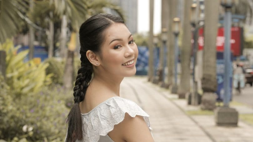 Asian woman with hair in triple braid smiling