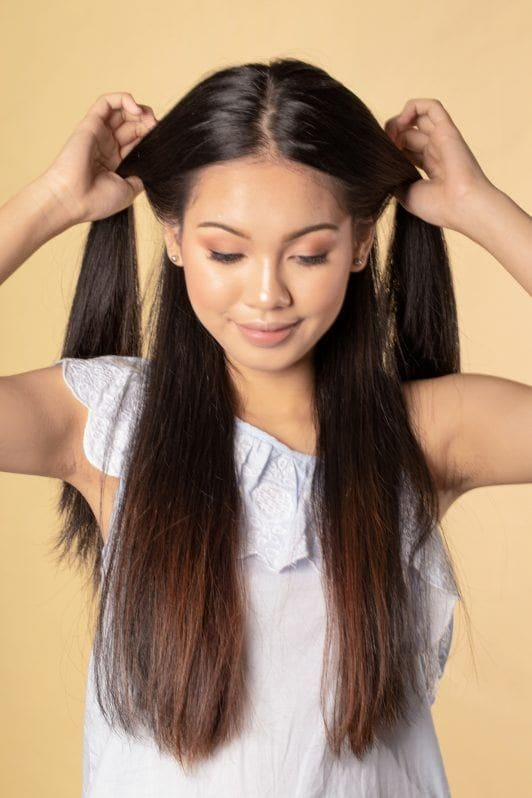 Asian woman holding two sections of her long hair