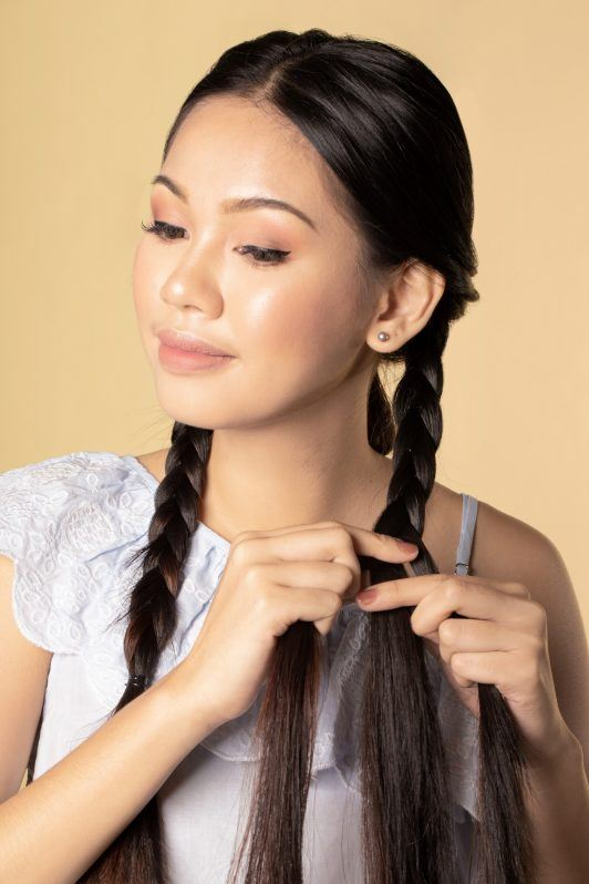 Asian woman creating triple braid