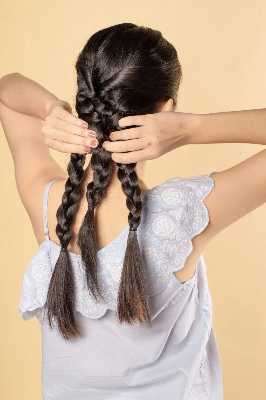 Back shot of Asian woman creating a triple braid