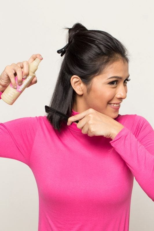 Wet look for short hair: Asian woman spraying on hair