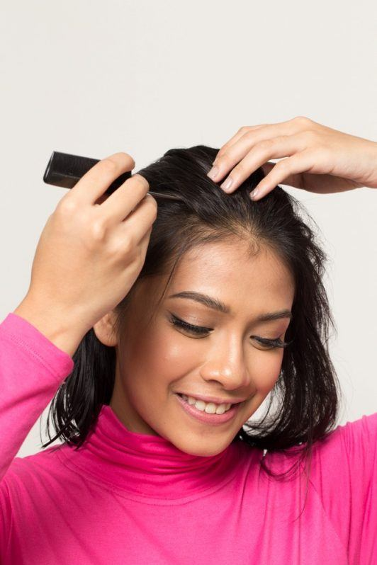 Asian woman parting her hair