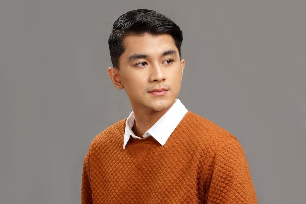 Asian man with a side part haircut wearing a brown polo