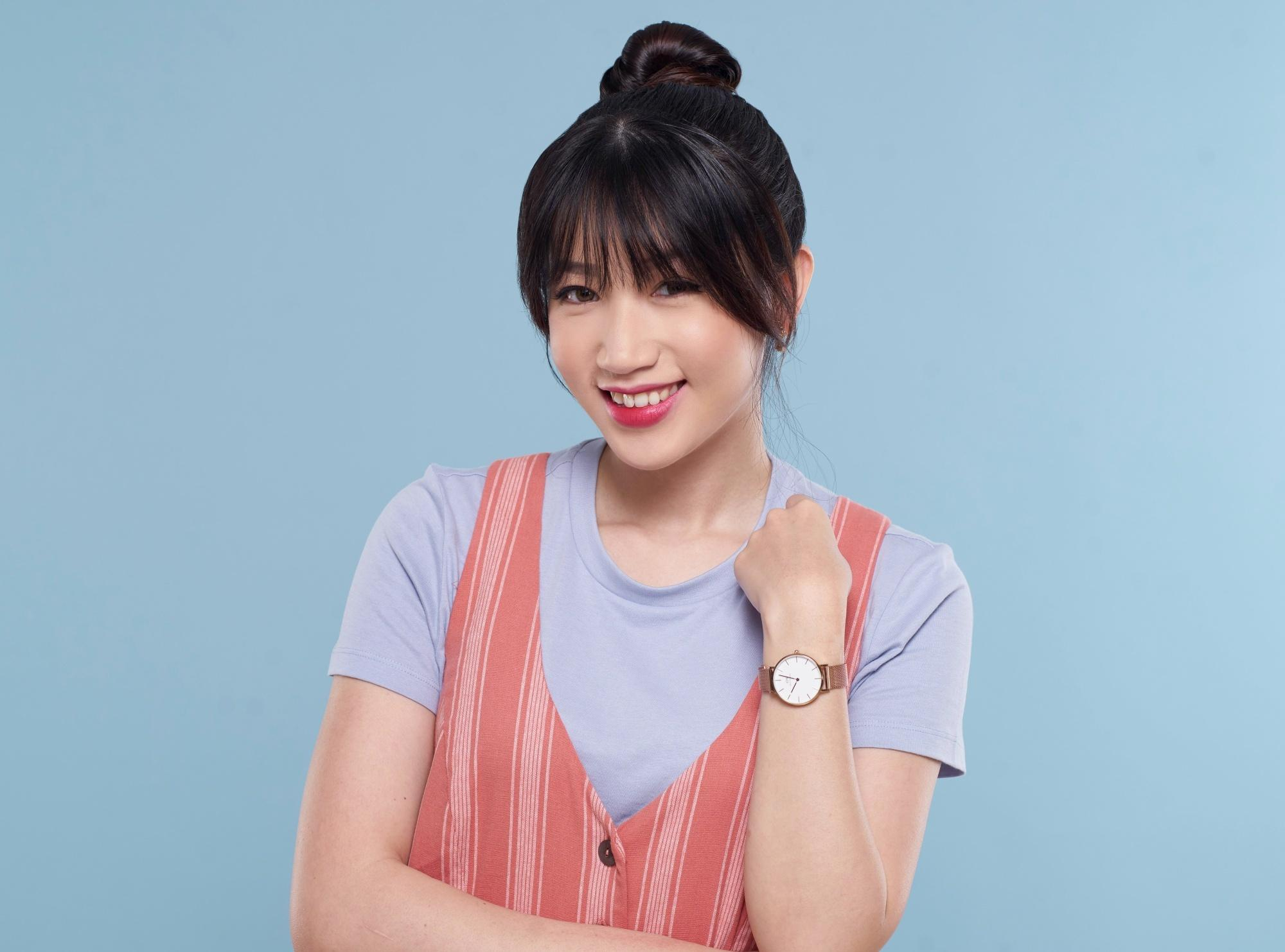 Asian woman with black hair with bangs sporting a top knot hairstyle