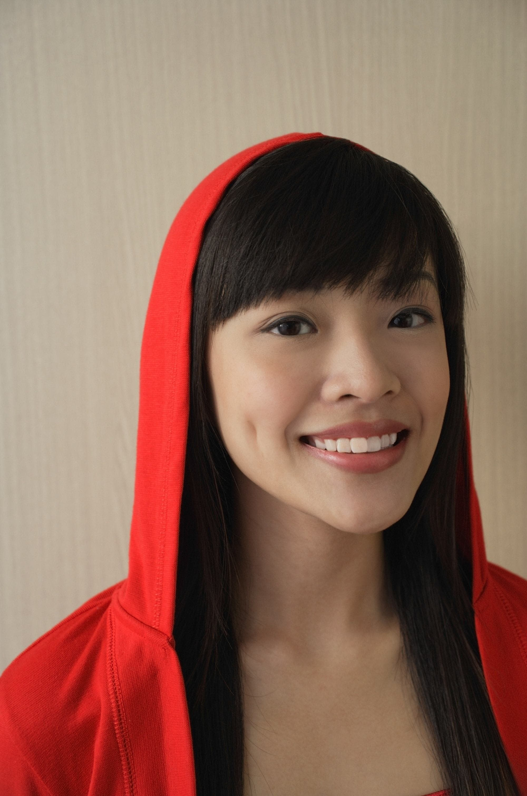 Asian woman with black hair and wispy bangs, wearing a red hoodie
