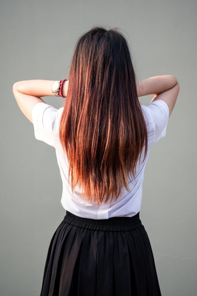 Back shot of an Asian woman with long mahogany brown hair with highlights