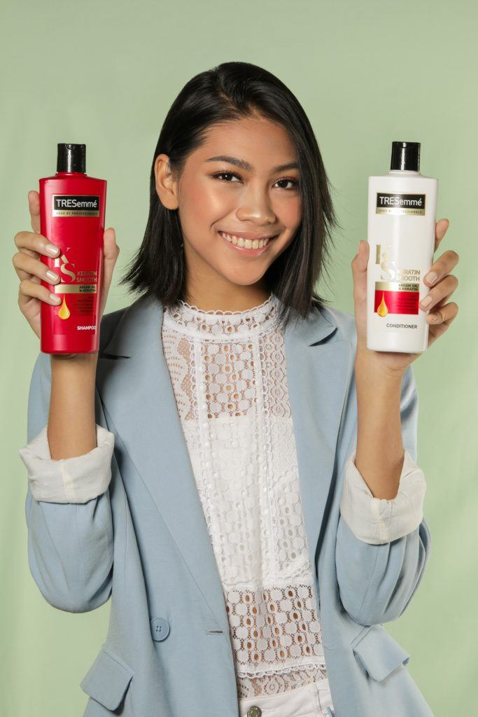 Center part bob: Asian woman with short hair holding shampoo and conditioner bottles