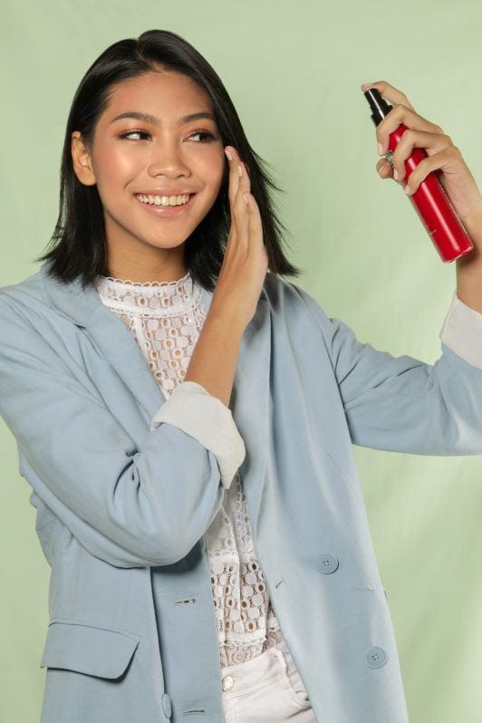 Center part bob: Asian woman spraying heat protectant on her short hair