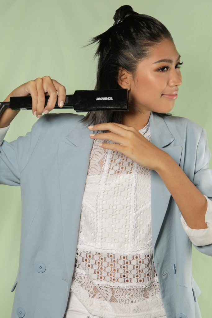 Asian woman ironing her short hair