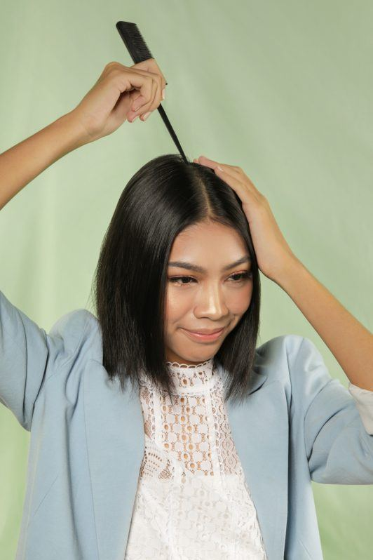 Asian woman creating a center part bob using a tail comb