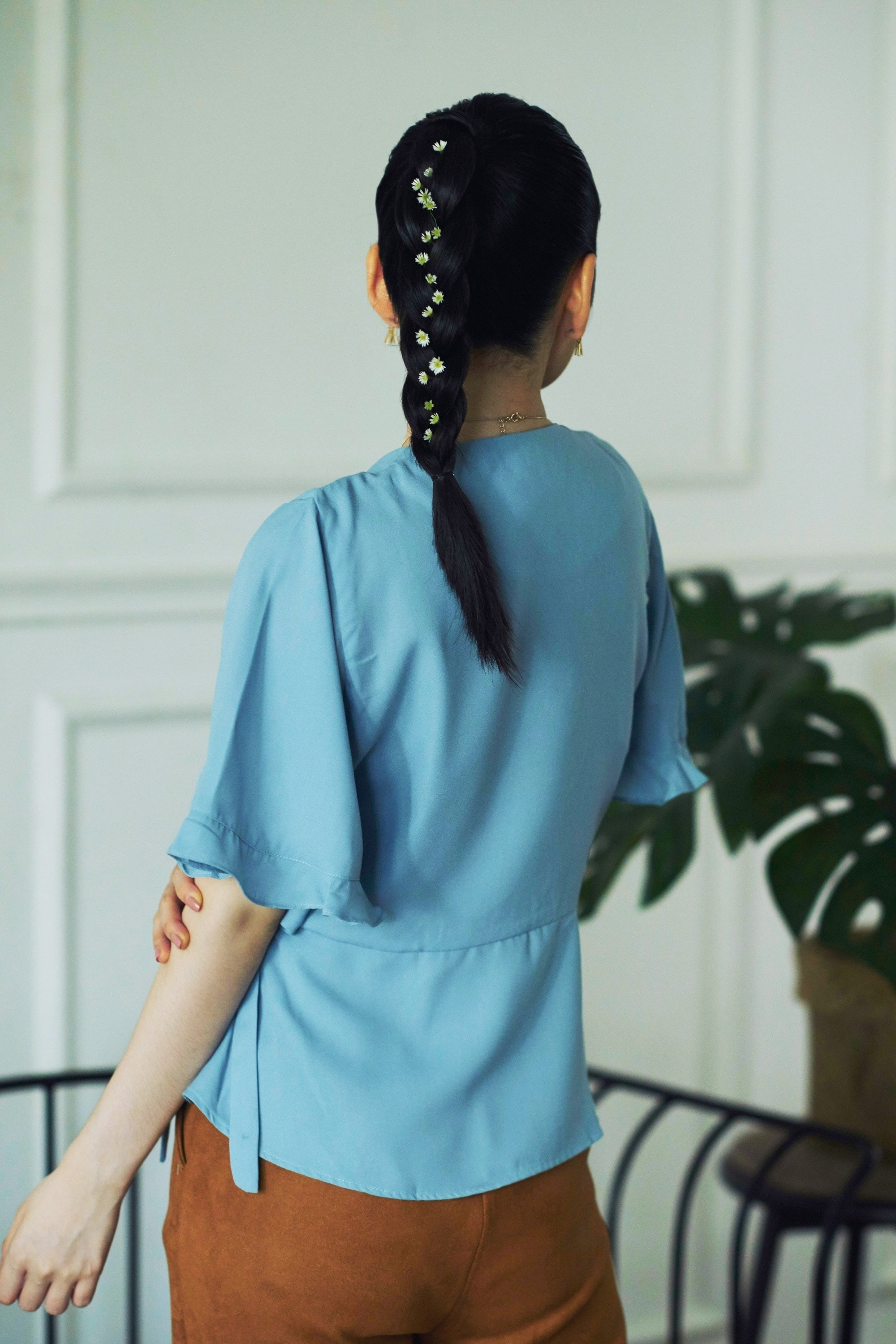 Back shot of an Asian woman with braid ponytail wearing a blue blouse