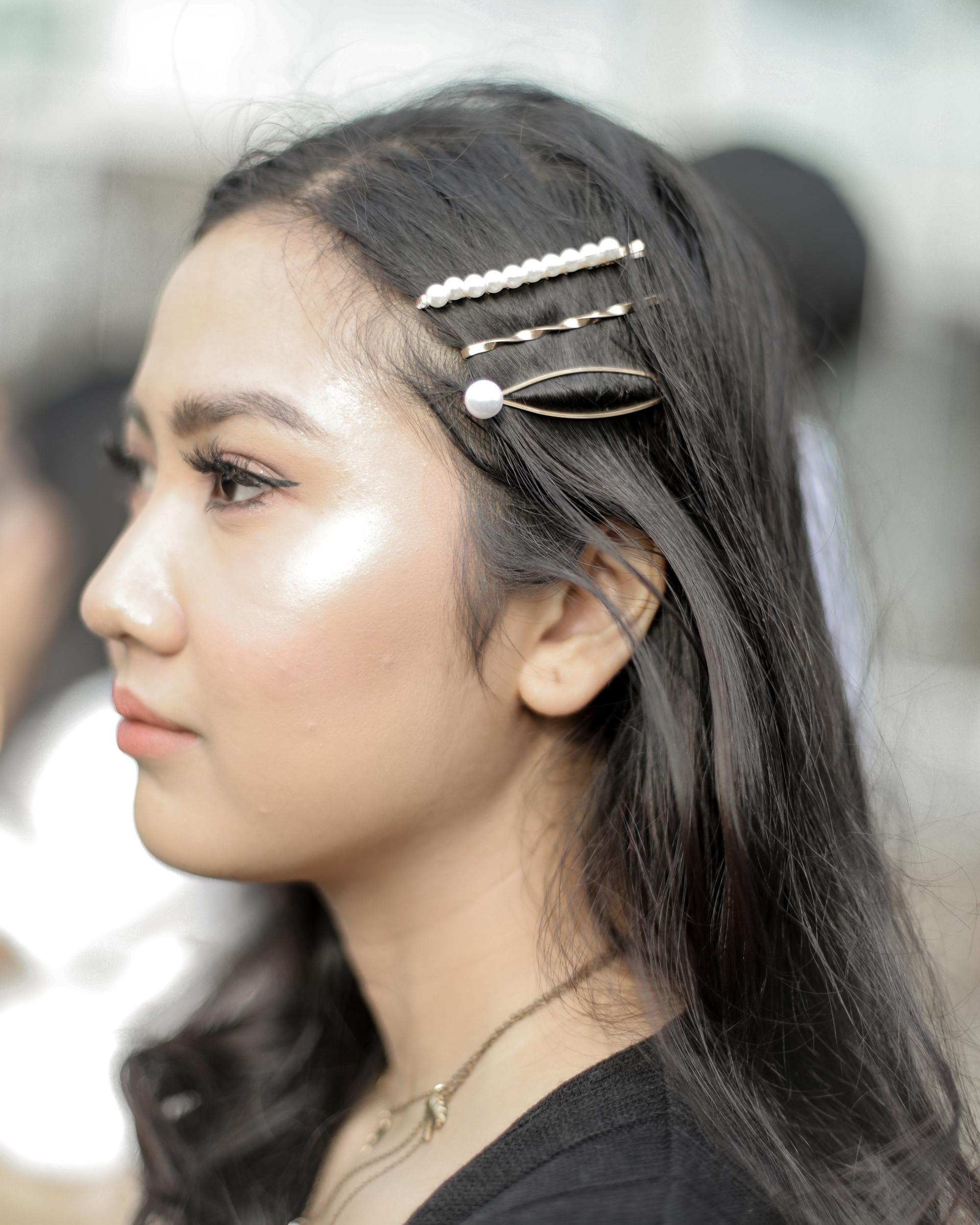 Side view of an Asian woman with different hair clips on her long black hair