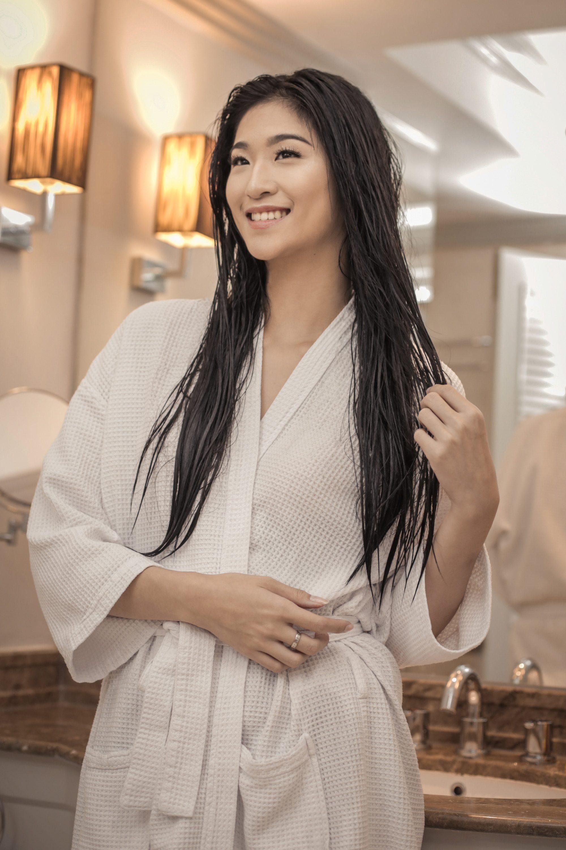 Hair vitamins: Asian woman with long damp hair wearing a white bathrobe