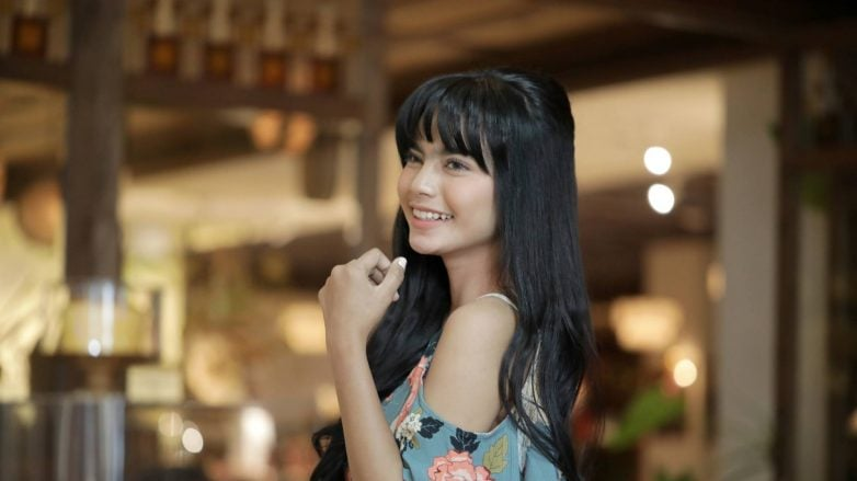Indonesian woman with long hair in half updo with bangs