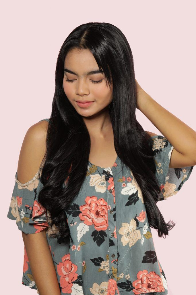 Half updo with bangs: Asian woman wearing a floral top, touching her hair