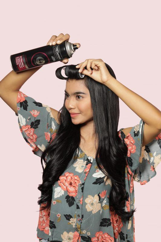 Half updo with bangs: Asian woman spritzing hair spray on her bangs rolled on velcro rollers