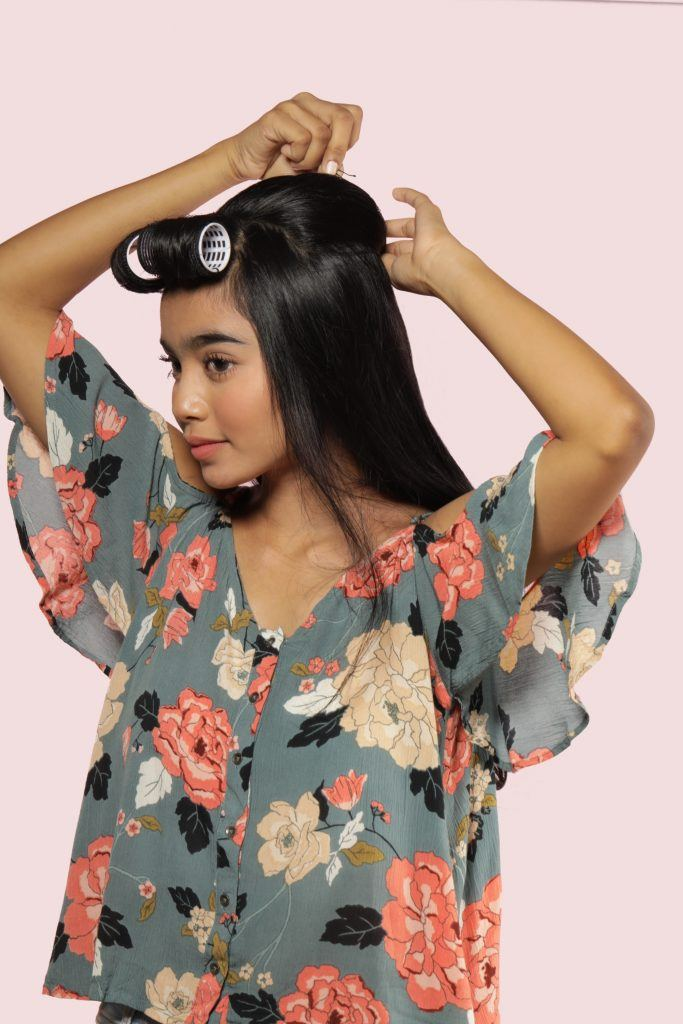 Half updo with bangs: Asian woman pinning her half updo hairstyle