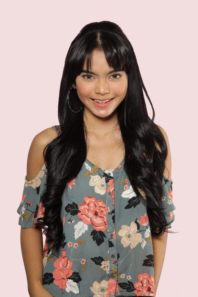 Asian woman wearing a floral top, smiling to the camera with her half updo with bangs