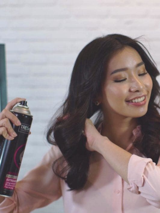How to blow out hair: Asian woman spritzing hairspray on her extra volume blown out hair