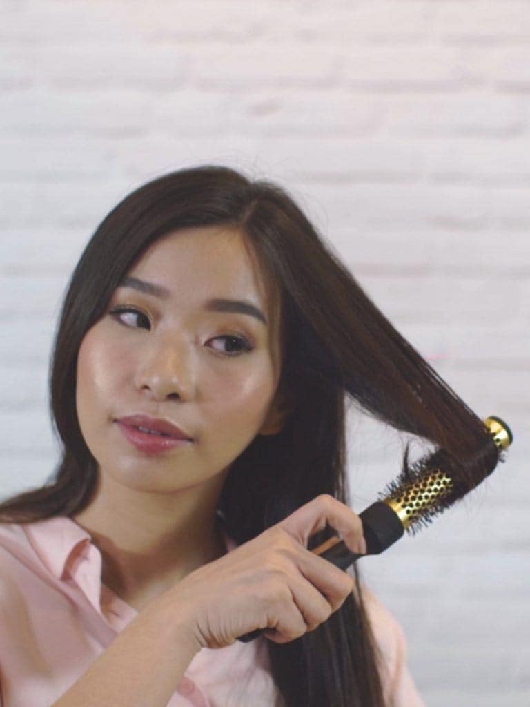 How to blow out hair: Asian woman rolling her hair with a small round brush