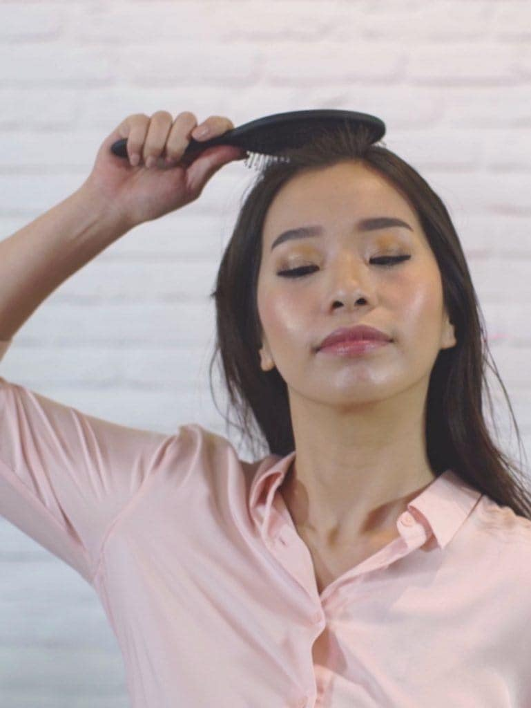How to blow out hair: Asian woman drying her hair using a wet brush