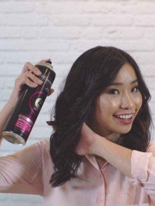 How to blow out hair: Asian woman spritzing hairspray on her loose curls blowout
