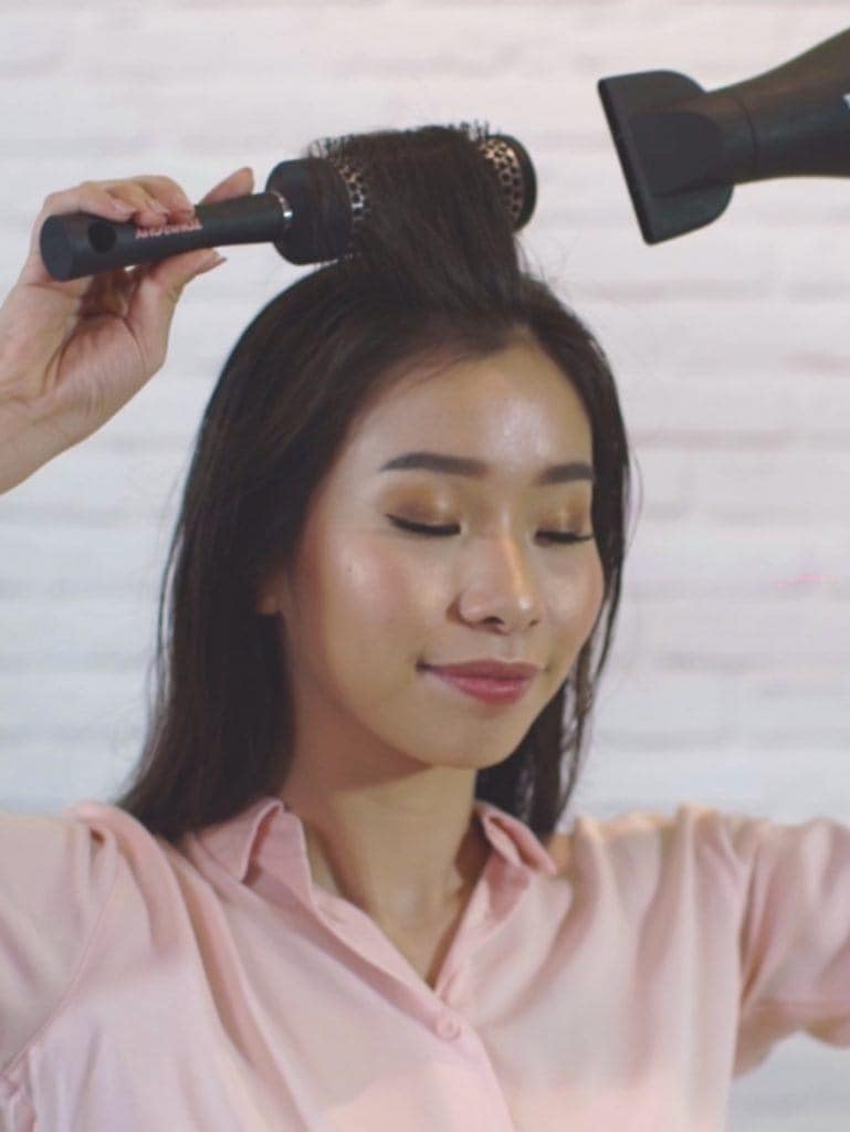 How to blow out hair: Asian woman brushing her hair using a round brush while blow drying