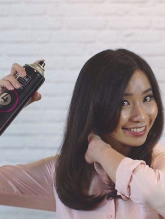 How to blow out hair: Asian woman spritzing hairspray on her traditional blowout
