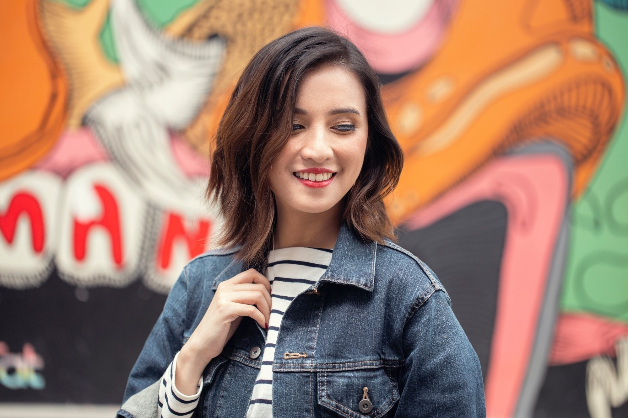 Asian woman wearing a denim jacket, smiling with her messy hair look