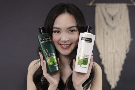 Asian woman wearing a white tank top and her hair down holding shampoo bottles