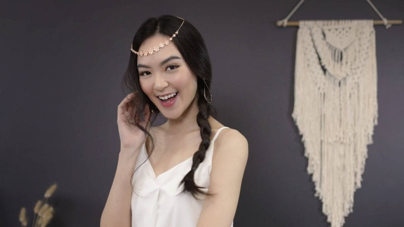 Asian woman with messy side braid with headband smiling at the camera