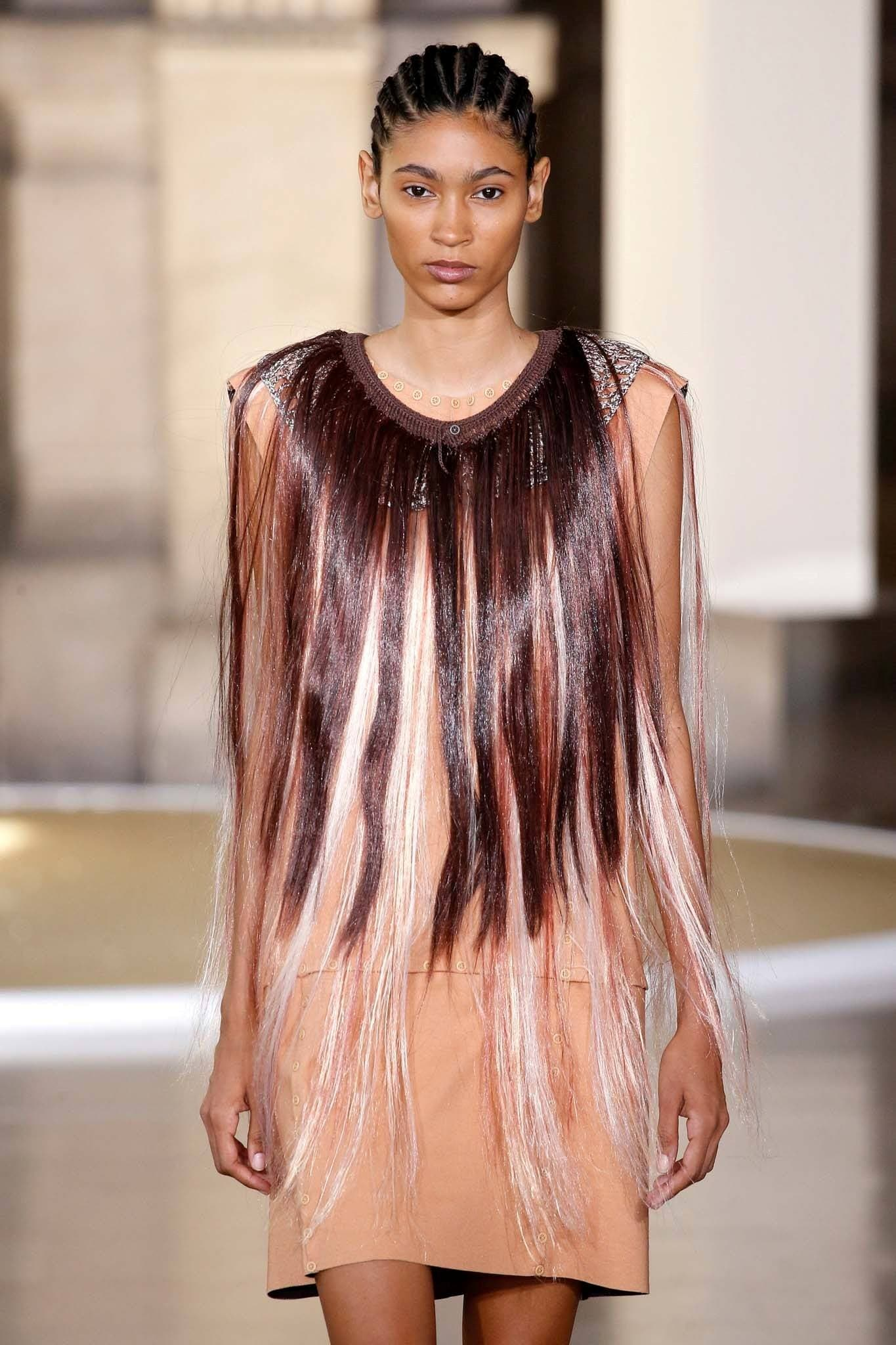 Paris fashion week haute couture model with cornrows hairstyle wearing a brown dress