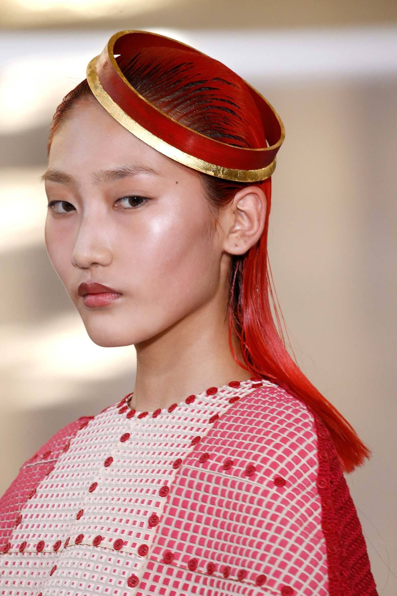 Asian model with red straight hair and a head gear