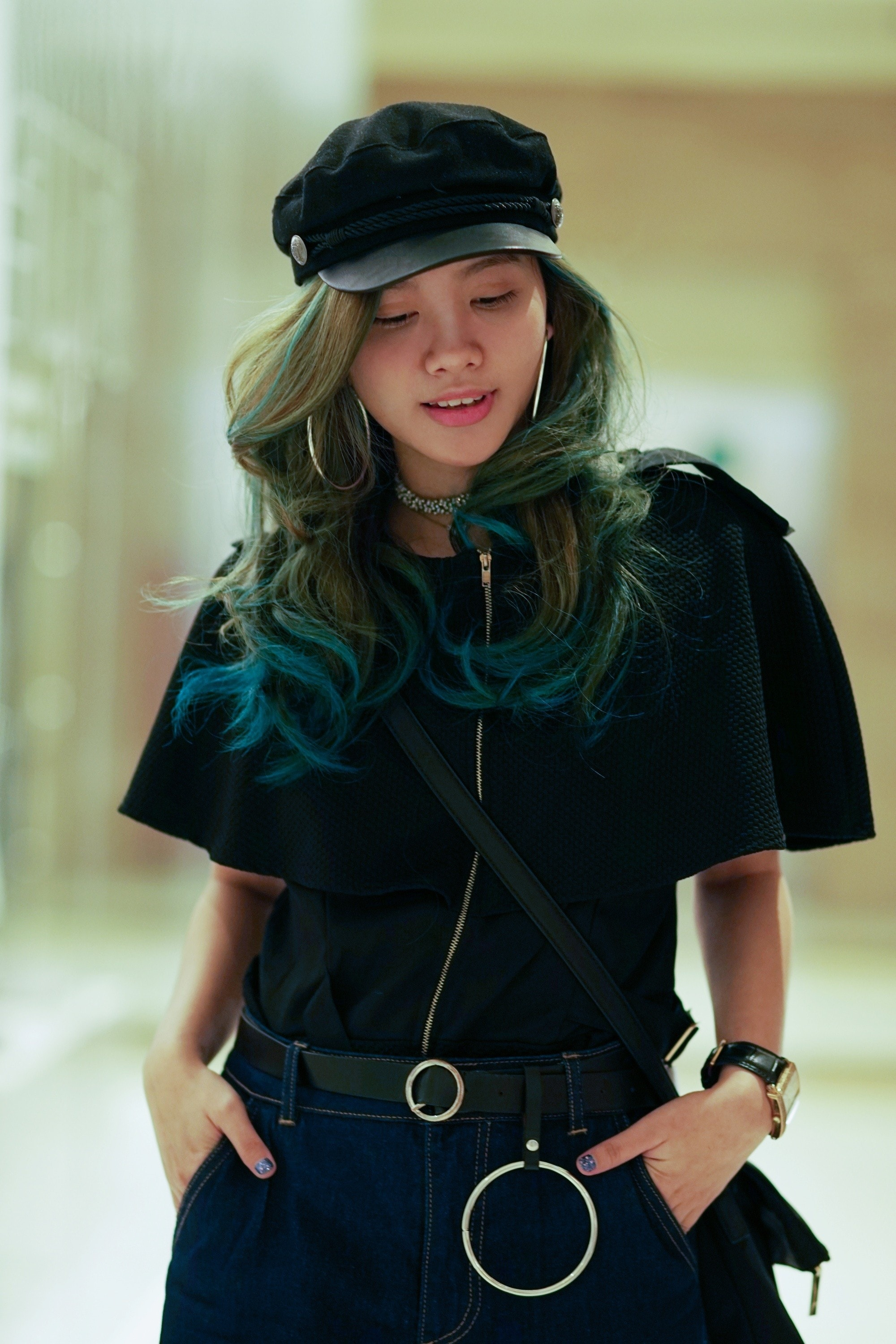 Asian woman with blue and green wavy hair wearing a hat