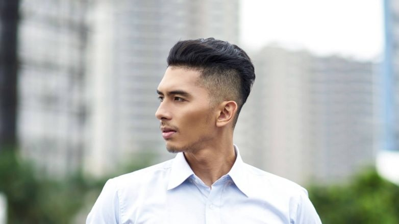 Shampoo for Men: Asian man with shaved side hairstyle wearing a white long sleeved polo outdoors