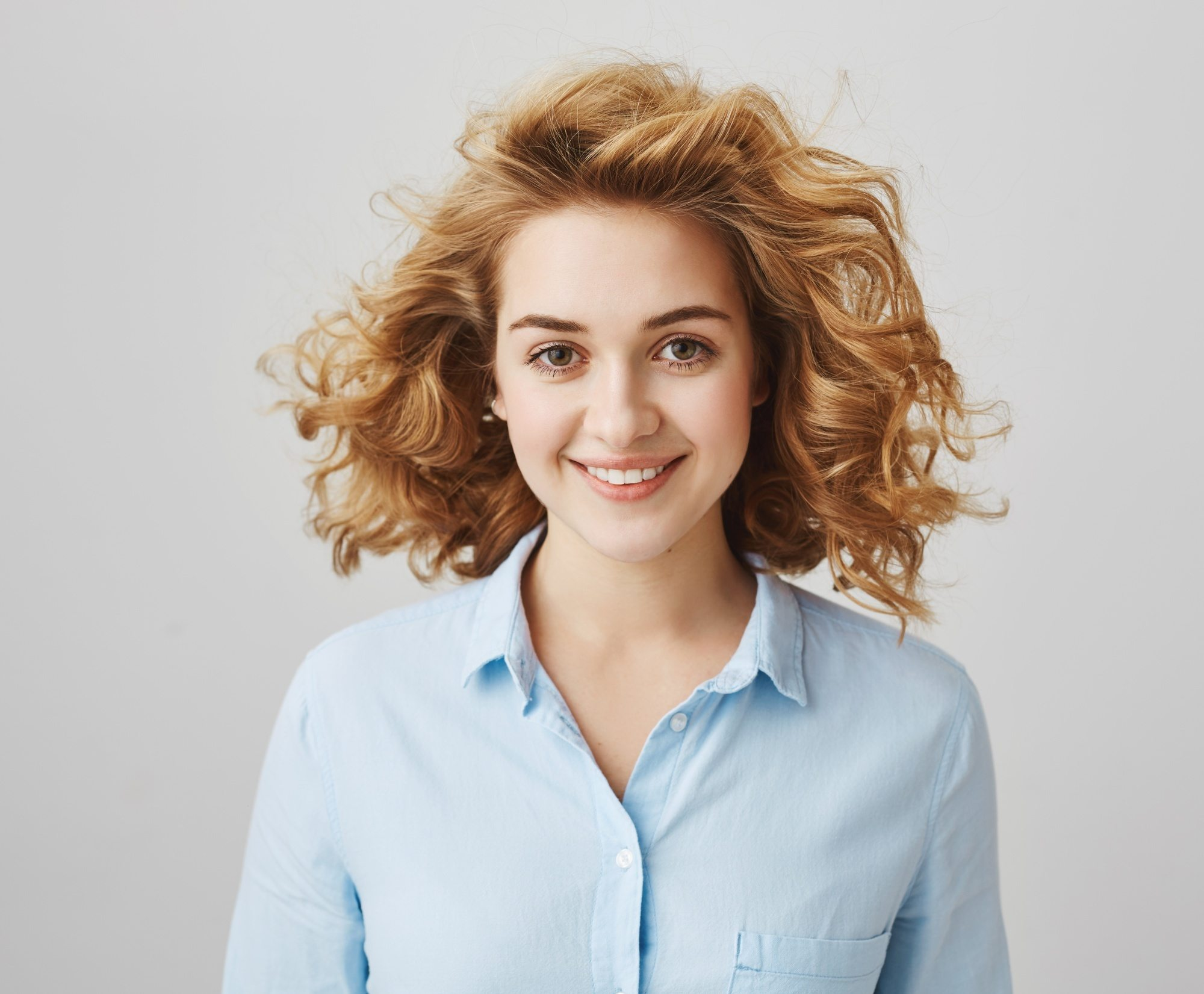 Short wavy hair ideas: Woman with brown curly hair smiling