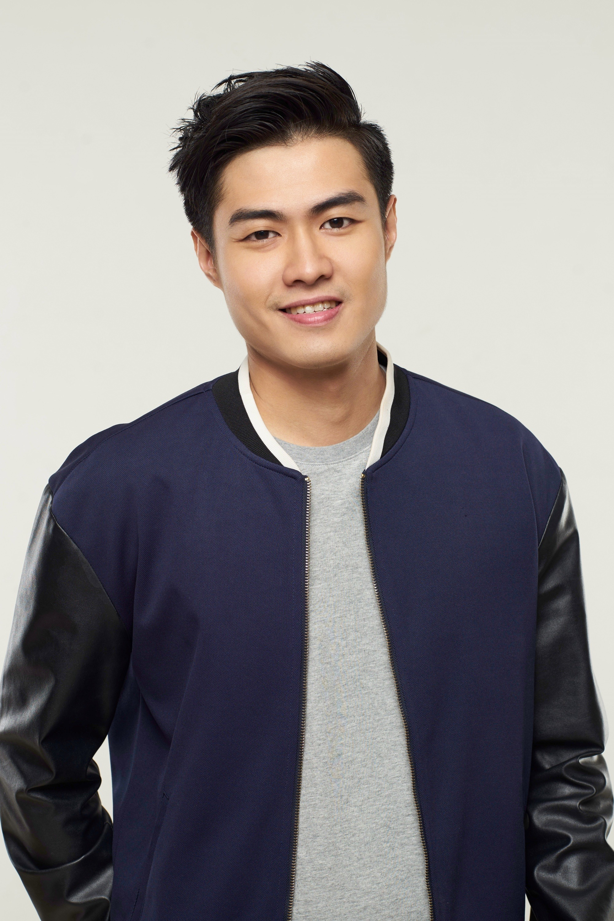 Asian man with side part haircut smiing and wearing a blue jacket