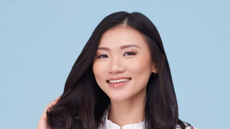 White hair causes: Asian woman touching her black shoulder-length hair smiling