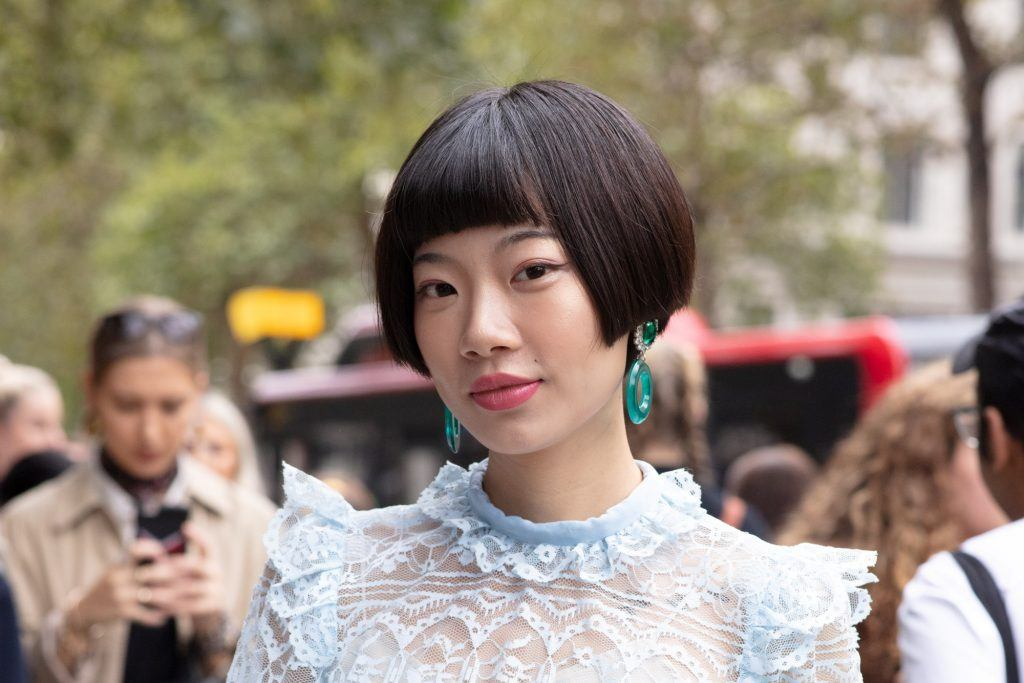 Asian woman with short black hair with bangs