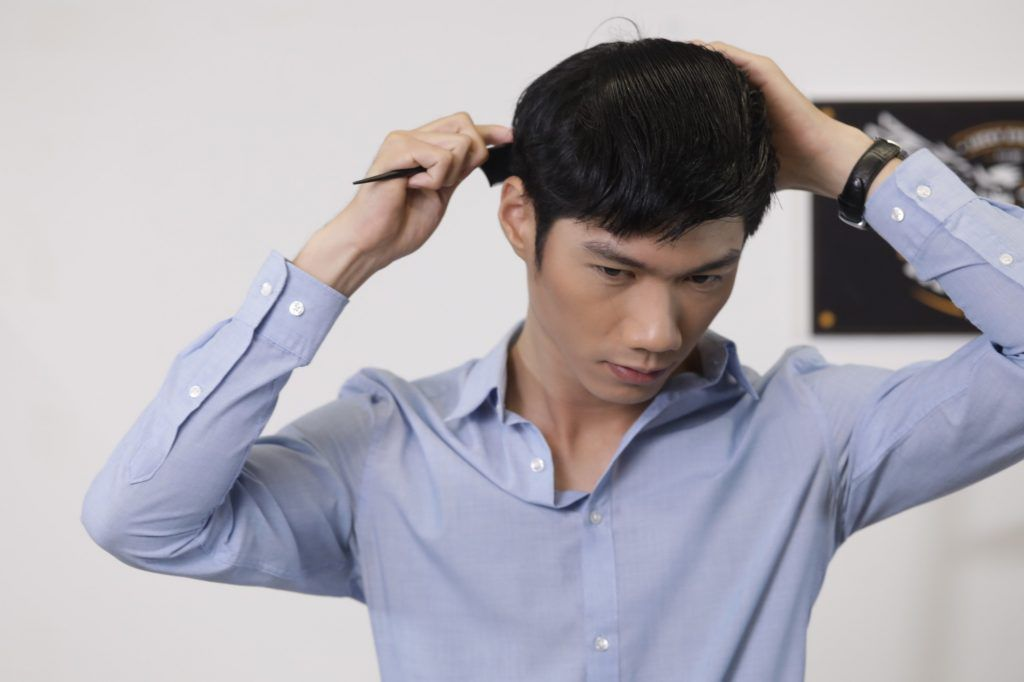 textured bowl cut for men: guy is combing his hair to remove tangles