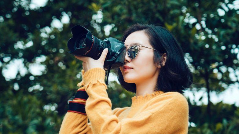 Asian woman taking pictures with camera