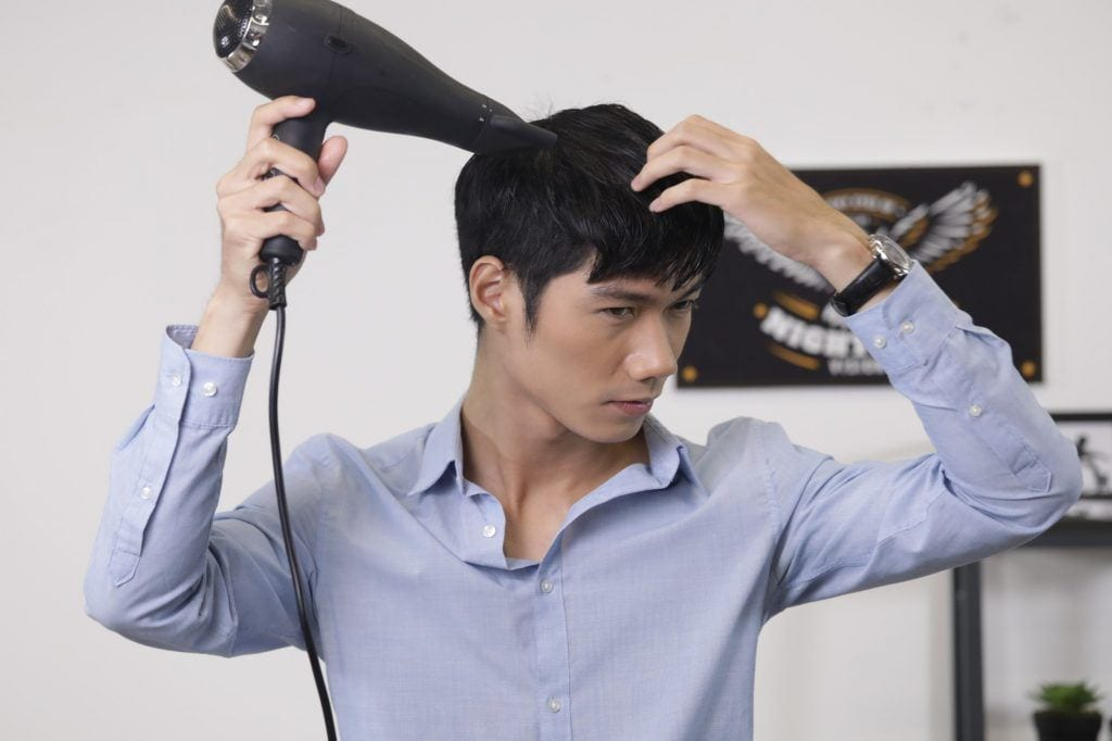 guy is holding a blow-dryer and pointing it to his hair