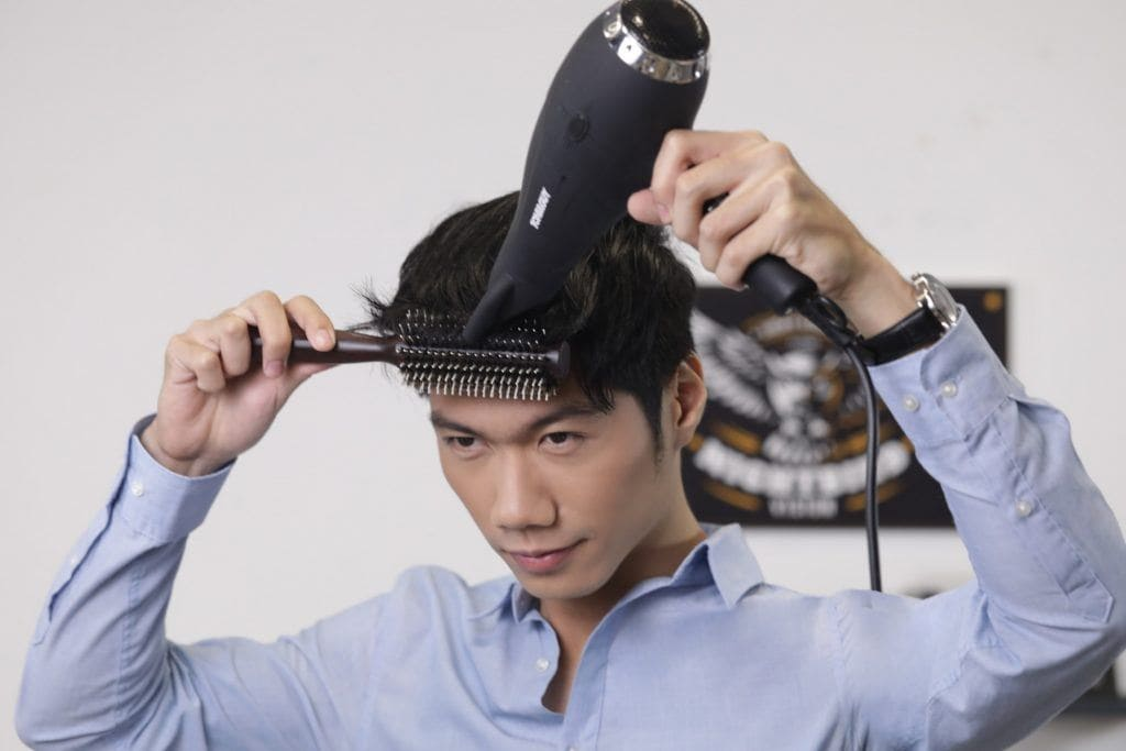 textured bowl cut for men: guy is using a brush and a blow-dryer on his hair