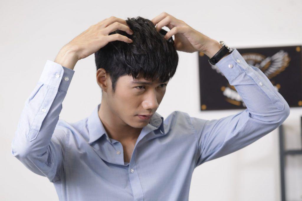Guy is applying something on his hair