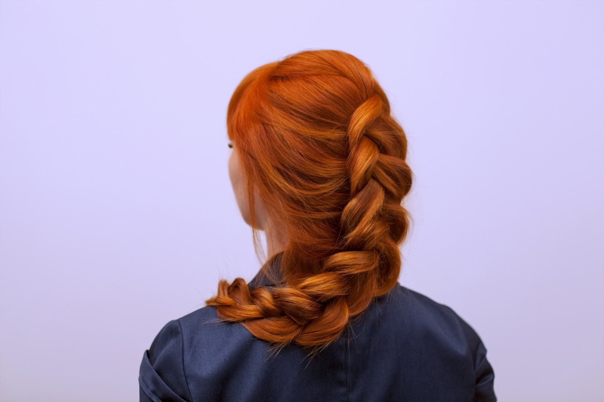 Bleached hair colors: back of a woman with a braided coral copper hair