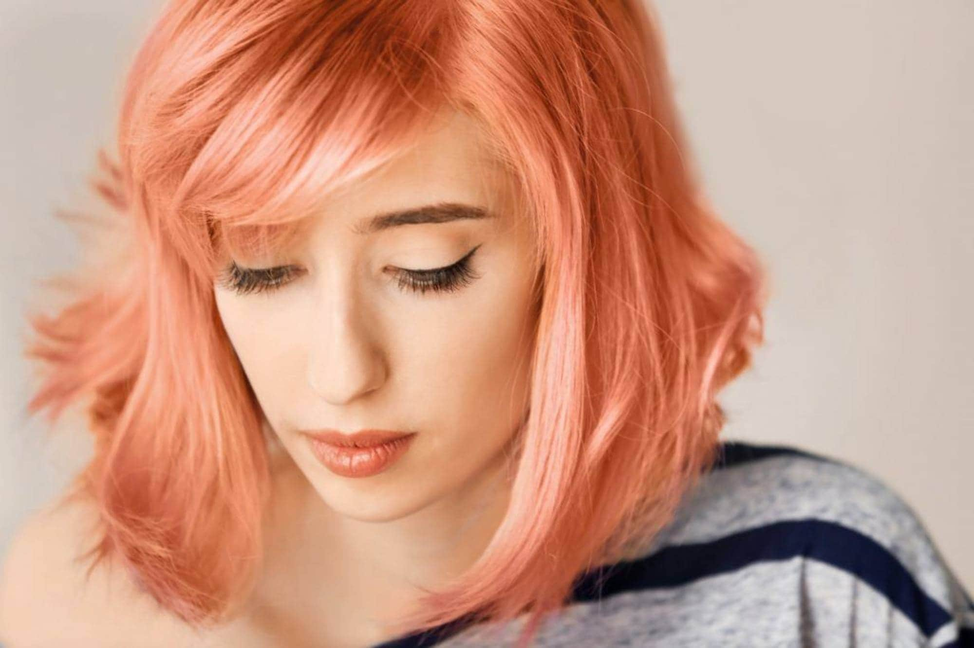 Bleached hair colors: a woman with her hair in a shade of coral