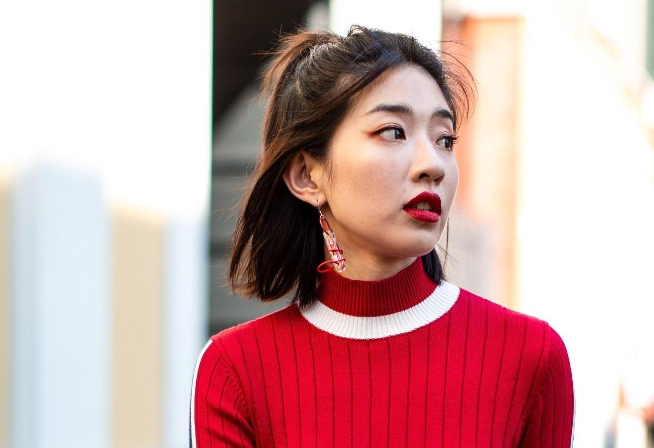 Asian woman with medium-length straight hair in a half updo wearing a red sweater outdoors