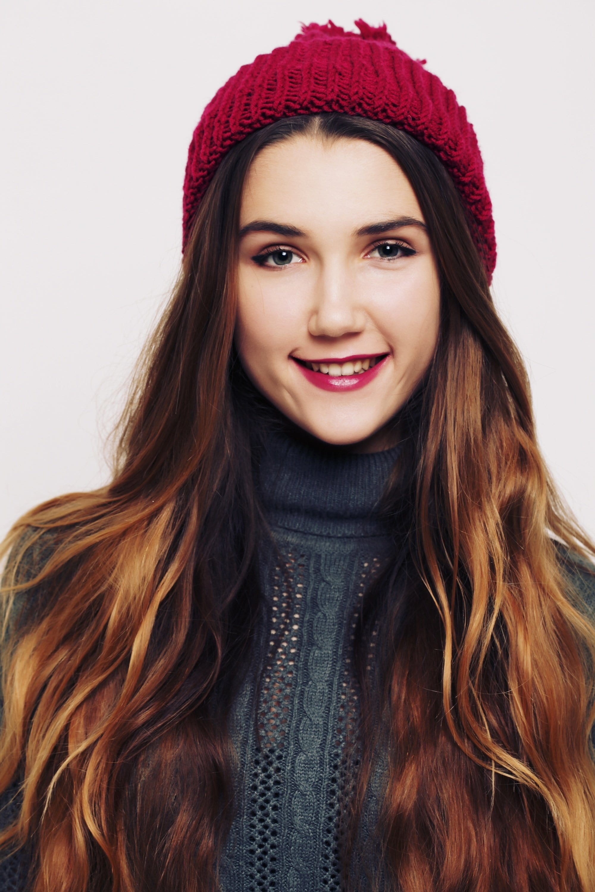woman wearing a red beanie on her copper balayage hair