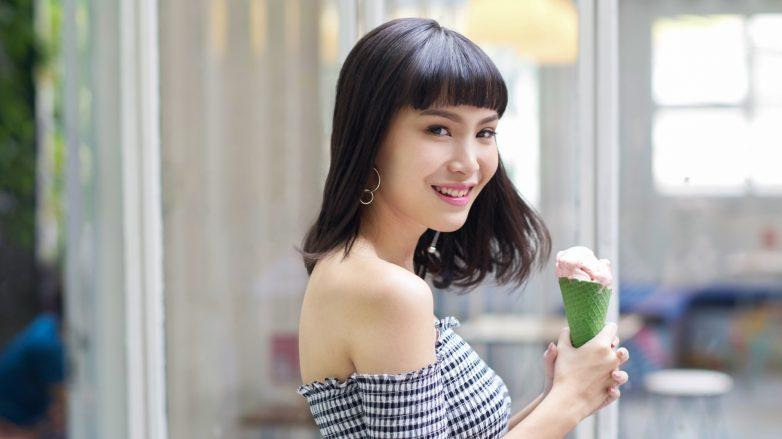 Filipino hair expressions: Asian woman with bangs, wearing an off-shoulder top, smiling to the camera while holding a cone of ice cream
